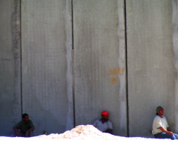 Three people by the wall near the Qalandiya Checkpoint (Photo credit: Bright Tal (Political))